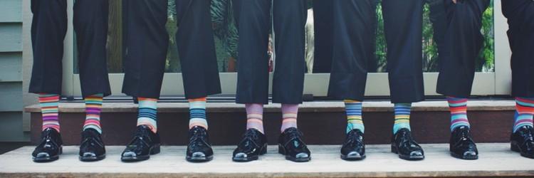 Teambuilding. Beine in Businesskleidung mit bunten Ringelsocken